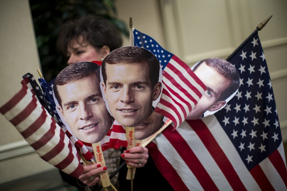 A supporter carries flags and photos of Conor Lamb at an election night event for Lamb, Democratic congressional candidate for Pennsylvania's 18th district, on March 13, 2018 in Canonsburg, Pa. (Drew Angerer/Getty Images)