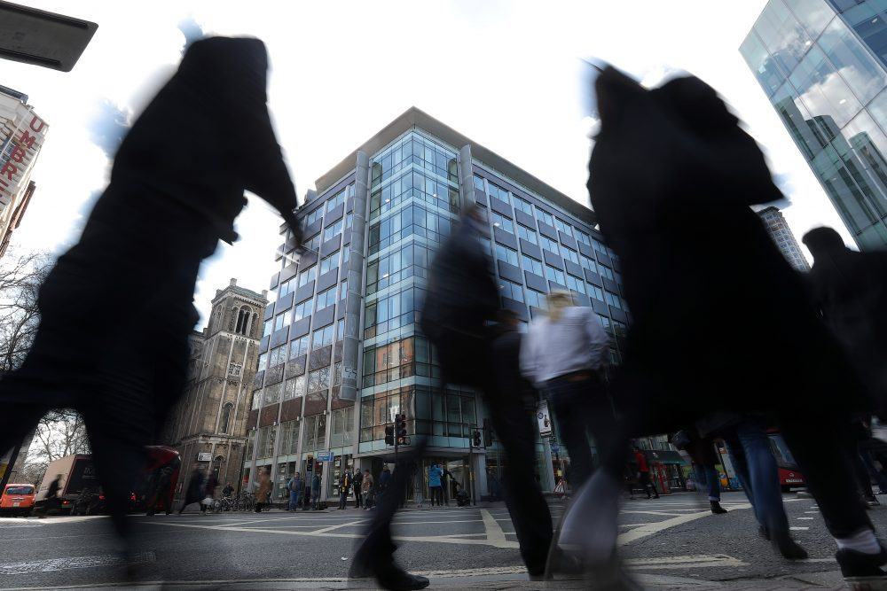 Pedestrians pass the shared building which houses the offices of Cambridge Analytica in central London on March 21, 2018. Facebook expressed outrage Tuesday over the misuse of its data as Cambridge Analytica, the British firm at the center of a major scandal rocking the social media giant, suspended its chief executive. (Daniel Leal-Olivas/AFP/Getty Images)