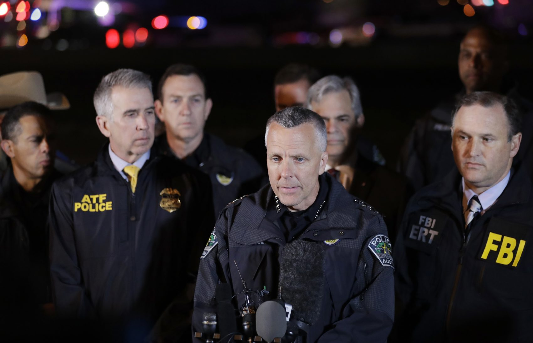 Austin Police Chief Brian Manley, center, stands with other members of law enforcement as he briefs the media, Wednesday, March 21, 2018, in the Austin suburb of Round Rock, Texas. The apparent suspect in a spate of bombing attacks that have terrorized Austin over the past month blew himself up with an explosive device as authorities closed in, the police said early Wednesday. (AP Photo/Eric Gay)