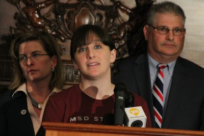 Erin Heim, of Somerville, a 2008 graduate of the Marjory Stoneman Douglas High, speaks at the State House with extreme risk protective order bill sponsors Rep. Marjorie Decker, left, and Rep. David Linsky. (Sam Doran/State House News Service)