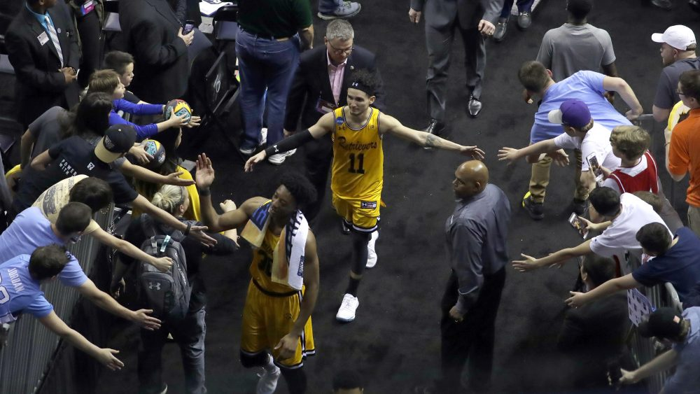 UMBC's K.J. Maura (11) greets fans as he leaves the court after the team's second-round game against Kansas State in the NCAA men's college basketball tournament in Charlotte, N.C., Sunday. Kansas State won 50-43. (Chuck Burton/AP)