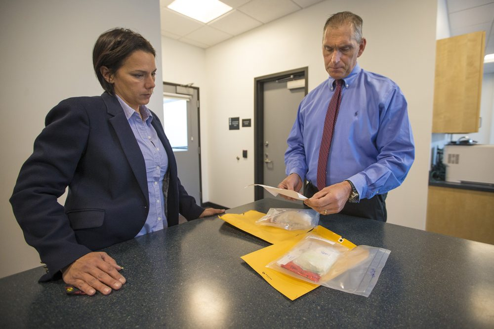 "Arlington Police Chief Fred Ryan, right, and inspector Gina Bassett review toxicology reports on cocaine evidence, looking for the possibility of fentanyl. ""Law enforcement tells us that the next wave of the addiction crisis is fentanyl-laced cocaine,"" Ryan says. (Jesse Costa/WBUR)"