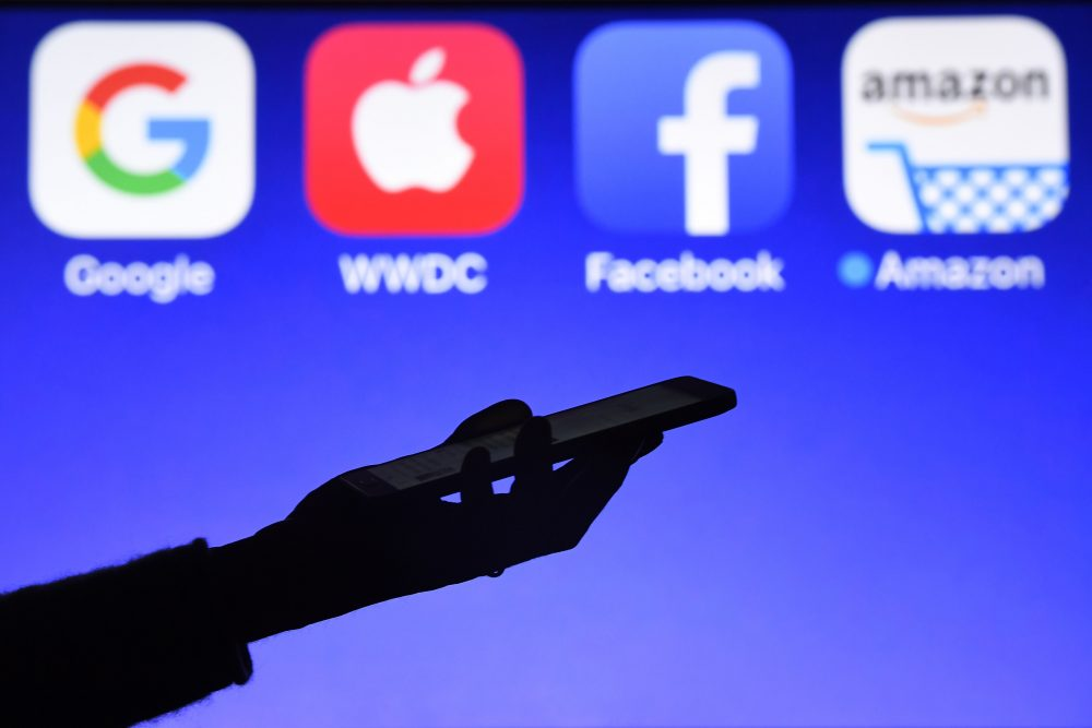 This photograph taken on Sept. 28, 2017, shows a smartphone being operated in front of logos for Google, Apple, Facebook and Amazon, in Hédé-Bazouges, western France. (Damien Meyer/AFP/Getty Images)