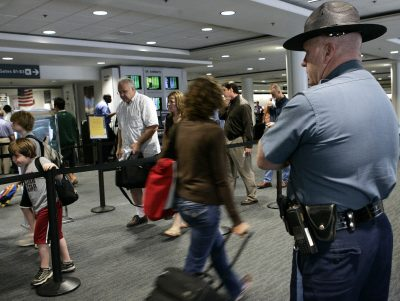 In this 2006 file photo, a Massachusetts state trooper keeps watch over travelers making their way through Logan International Airport in Boston. (Elise Amendola/AP)