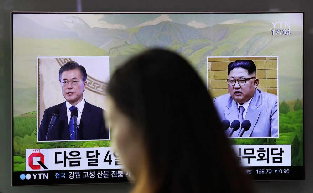 A visitor walks by a TV screen showing file footages of South Korean President Moon Jae-in, left, and North Korean leader Kim Jong Un, right, during a news program at the Seoul Railway Station in Seoul, South Korea, Thursday, March 29, 2018. North Korean leader Kim will meet South Korean President Moon at a border village on April 27, the South announced Thursday after the nations agreed on a rare summit that could prove significant in global efforts to resolve a decades-long standoff over the North's nuclear program. (Lee Jin-man/AP)