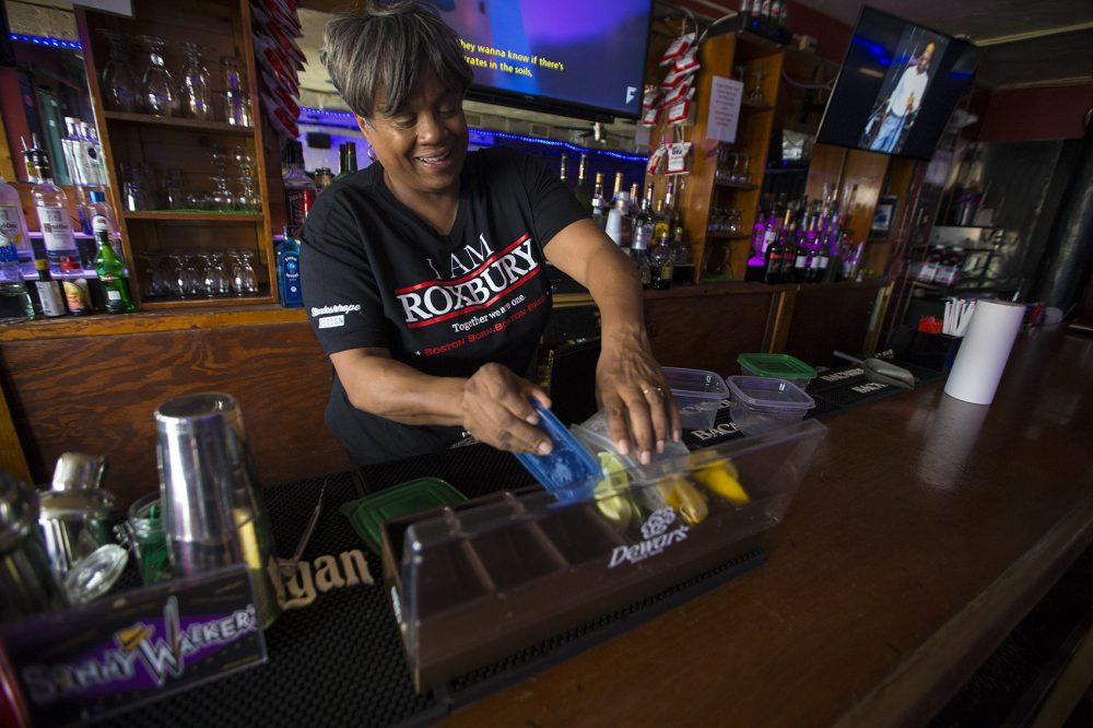 Andrea Walker preps the bar at Sonny Walker's before opening. (Jesse Costa/WBUR)