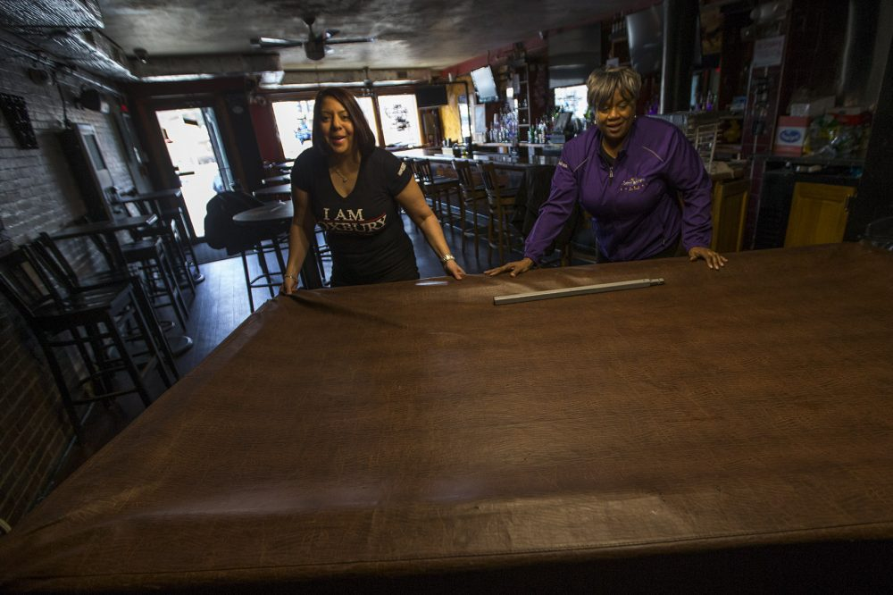 Mia McIlvany and Andrea Walker move the pool table out of the way to make room for that evening's entertainment. (Jesse Costa/WBUR)