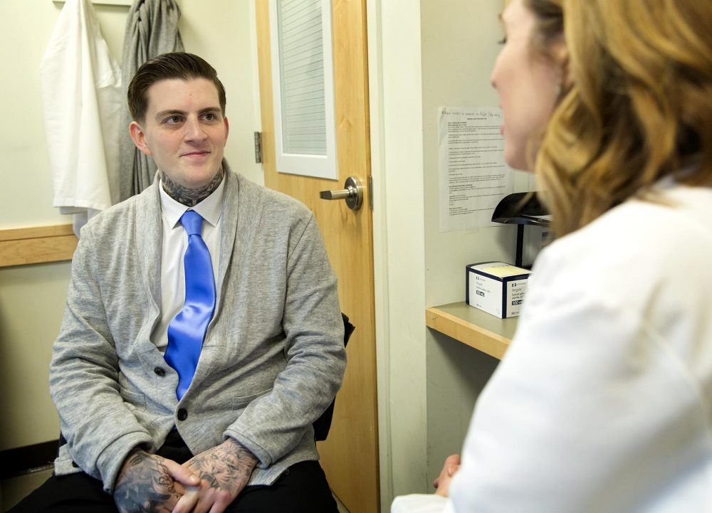 Patient Ricky Scimeca, 28, a barber from Boston, talks with Dr. Laura Kehoe at MGH's Bridge Clinic. (Robin Lubbock/WBUR)