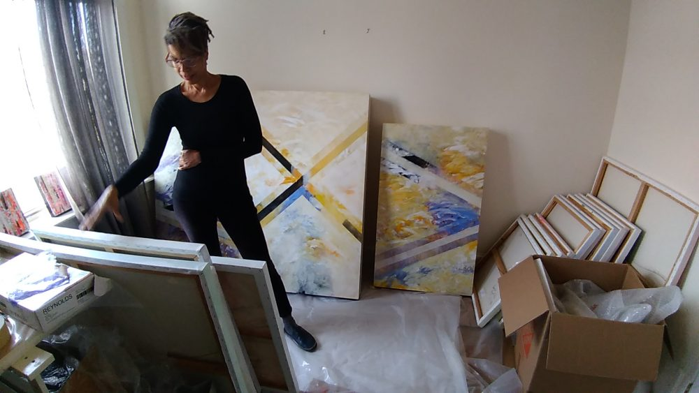 Artist Pamela Reynolds sorts through her paintings. (Courtesy)