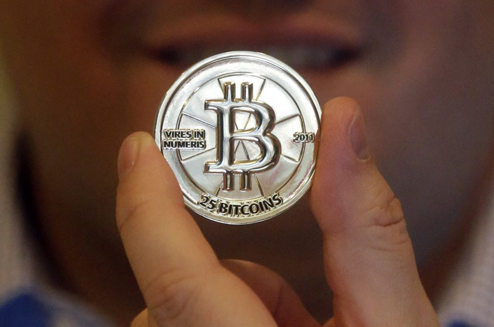 In this 2013 file photo, Mike Caldwell holds a 25 Bitcoin token at his shop in Sandy, Utah. (Rick Bowmer/AP)