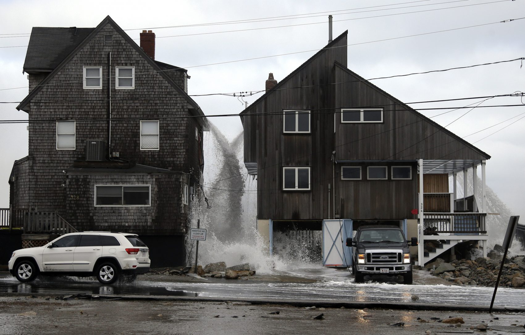 Ocean water pours off the roofs of these beachfront homes, Tuesday, March 6, 2018, as high surf continues in Marshfield, Mass. Utilities are racing to restore power to tens of thousands of customers in the Northeast still without electricity after last week's storm as another nor'easter threatens the hard-hit area with heavy, wet snow, high winds, and more outages. (Elise Amendola/AP)