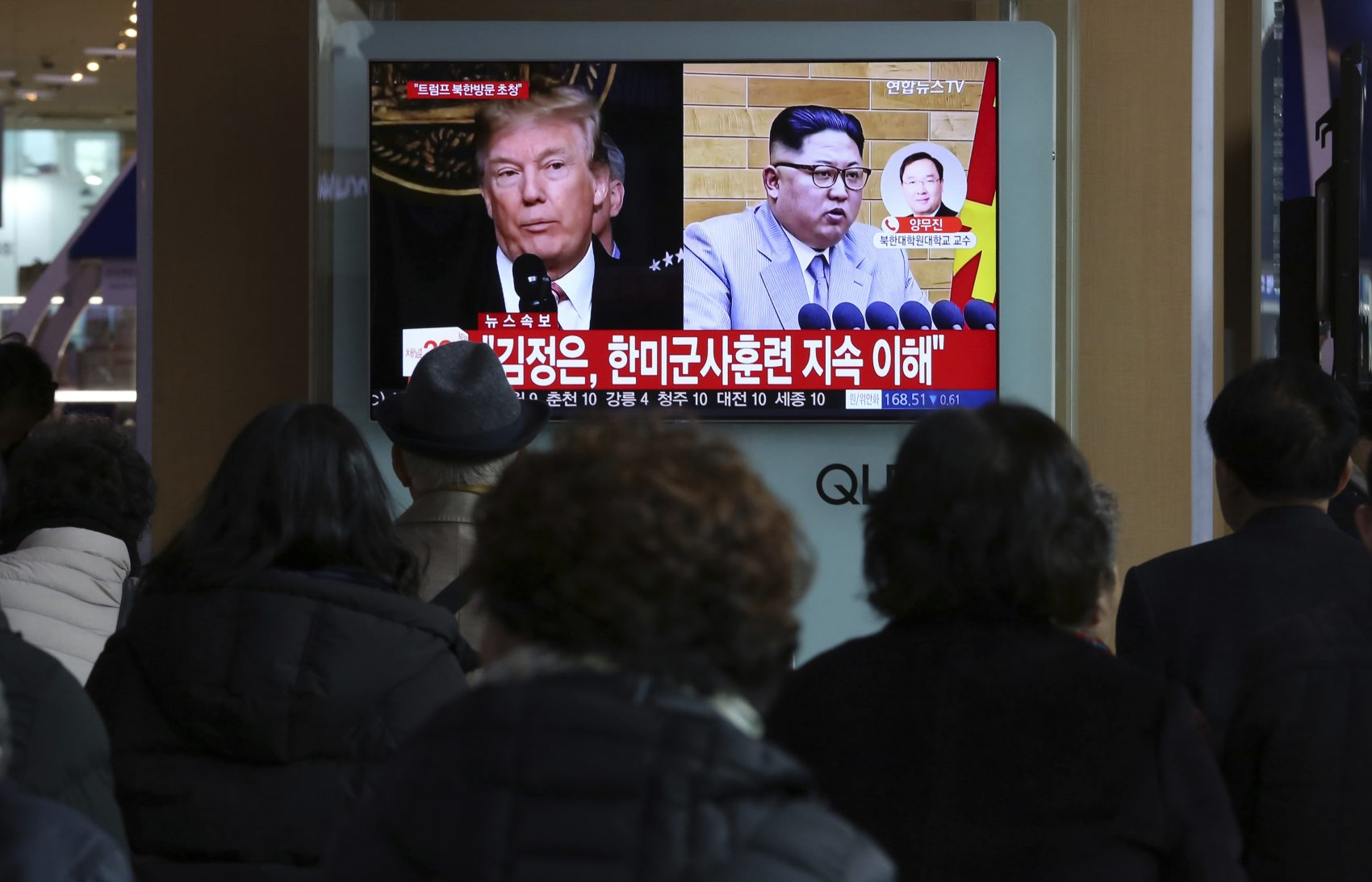 """People watch a TV screen showing North Korean leader Kim Jong Un and U.S. President Donald Trump, left, at the Seoul Railway Station in Seoul, South Korea, Friday, March 9, 2018. After months of trading insults and threats of nuclear annihilation, Trump agreed to meet with North Korean leader Kim Jung Un by the end of May to negotiate an end to Pyongyang's nuclear weapons program, South Korean and U.S. officials said Thursday. No sitting American president has ever met with a North Korea leader. The signs read: """" Kim Jong Un understands that the routine joint military exercises between the South Korean and the United States must continue."""" (Ahn Young-joon/AP)"""