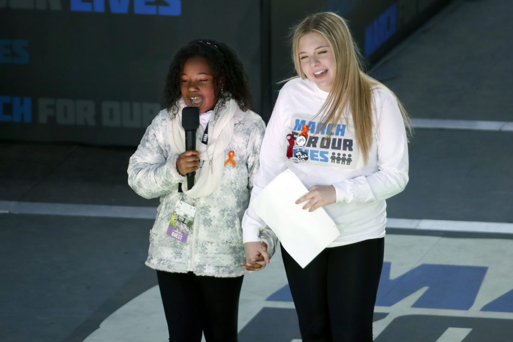 """Yolanda Renee King, grand daughter of Martin Luther King Jr., left, speaks as Jaclyn Corin, a student at Marjory Stoneman Douglas High School in Parkland, Fla., and one of the organizers of the rally, holds hands with her during the """"March for Our Lives"""" rally in support of gun control, Saturday, March 24, 2018, in Washington. (Alex Brandon/AP)"""