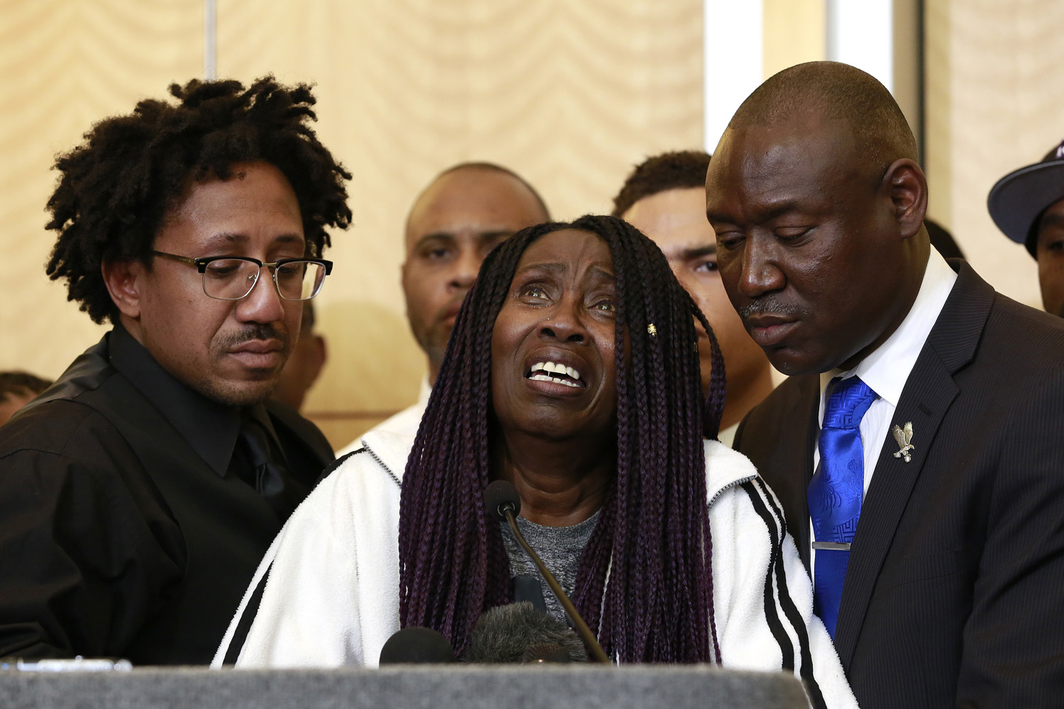 A tearful Sequita Thompson, center, pauses as she discusses the shooting of her grandson, Stephon Clark, during a news conference, Monday, March 26, 2018, in Sacramento, Calif. Clark, who was unarmed, was shot and killed by Sacramento police officers who were responding to a call about person smashing car windows a week ago. Thompson was accompanied by Clark's uncle, Kurtis Gordon, left, and attorney Ben Crump, right. (AP Photo/Rich Pedroncelli)