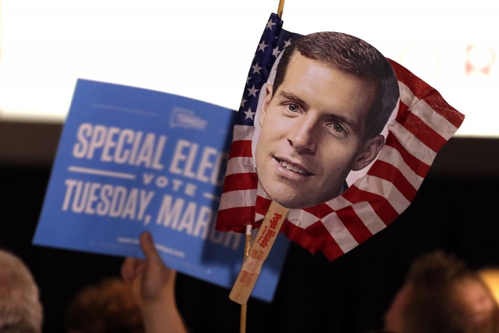 Supporters of Conor Lamb, the Democratic candidate for the March 13 special election in Pennsylvania's 18th Congressional District hold signs during his election night party in Canonsburg, Pa., Wednesday, March 14, 2018. Rattled Republicans were hit with the reality check Wednesday in the startling strong performance of a fresh-faced Democrat deep in Trump country.  (AP Photo/Gene J. Puskar)