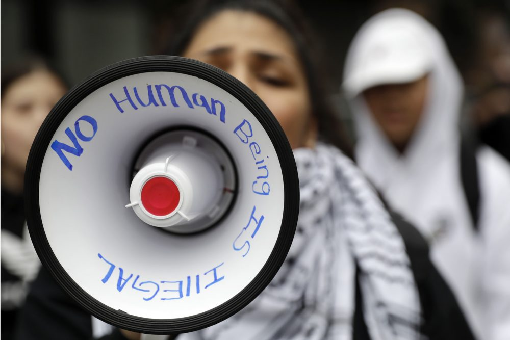 A demonstrator shouts slogans through a bullhorn outside of the Immigration and Customs Enforcement offices Wednesday, Feb. 28, 2018, in San Francisco. A top immigration official said Wednesday that about 800 people living illegally in Northern California were able to avoid arrest because of a weekend warning that Oakland Mayor Libby Schaaf put on Twitter.(AP Photo/Marcio Jose Sanchez)
