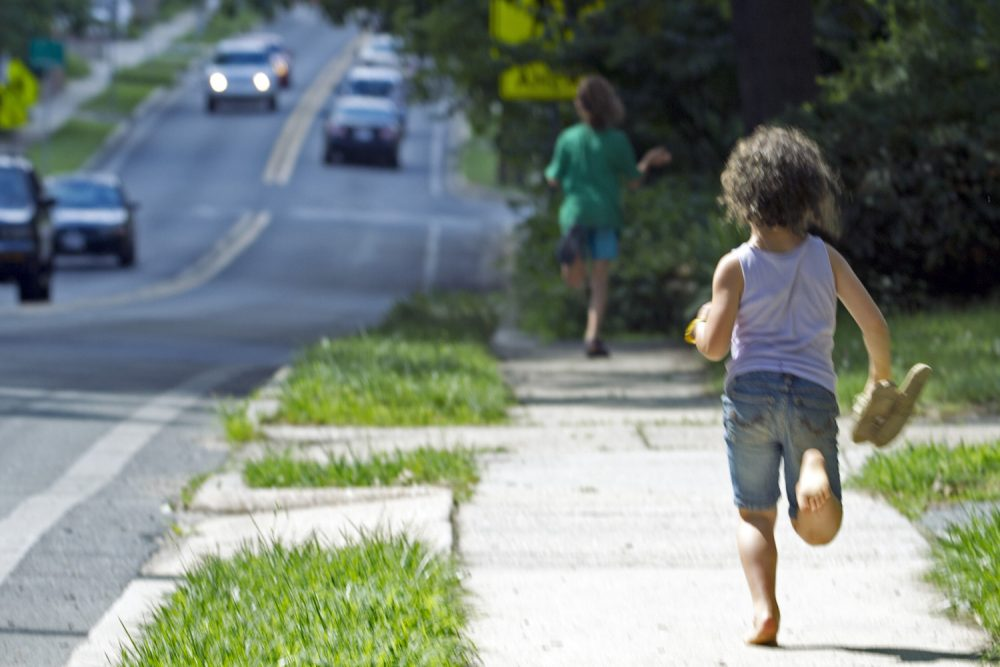 "Dvora Meitiv, 6, runs home with her brother Rafi 10,  after their mother Danielle Meitiv,pick them up at the school bus stop in Silver Spring Md., on Friday, June 12, 2015. After outcry over one family's ""free-range"" parenting case, Maryland officials on Friday clarified the state's policy on how authorities handle cases of children walking or playing alone outdoors, saying the state shouldn't investigate unless kids are harmed or face substantial risk of harm. (AP Photo/Jose Luis Magana)"