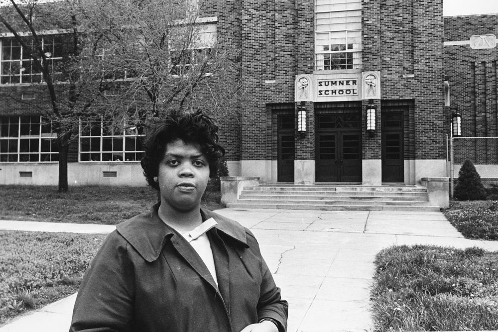 "FILE - This May 8, 1964 file photo shows Linda Brown Smith standing in front of the Sumner School in Topeka, Kansas. The refusal of the public school to admit Brown in 1951, then nine years old, because she is black, led to the Brown v. Board of Education of Topeka, Kansas. In 1954, the U.S. Supreme Court overruled the ""separate but equal"" clause and mandated that schools nationwide must be desegregated.  (AP Photo, File)"