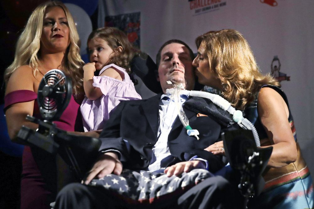 In this Sept. 18, 2017, photo, Pete Frates, who is stricken with  amyotrophic lateral sclerosis, or ALS, and is the inspiration of the Ice Bucket Challenge, , is kissed by his mother Nancy while appearing with his wife Julie and daughter Lucy at Fenway Park in Boston. Frates, whose challenge raised millions of dollars for research on Lou Gehrig's disease, is recovering from a health scare that landed him in the hospital. (AP Photo/Charles Krupa)