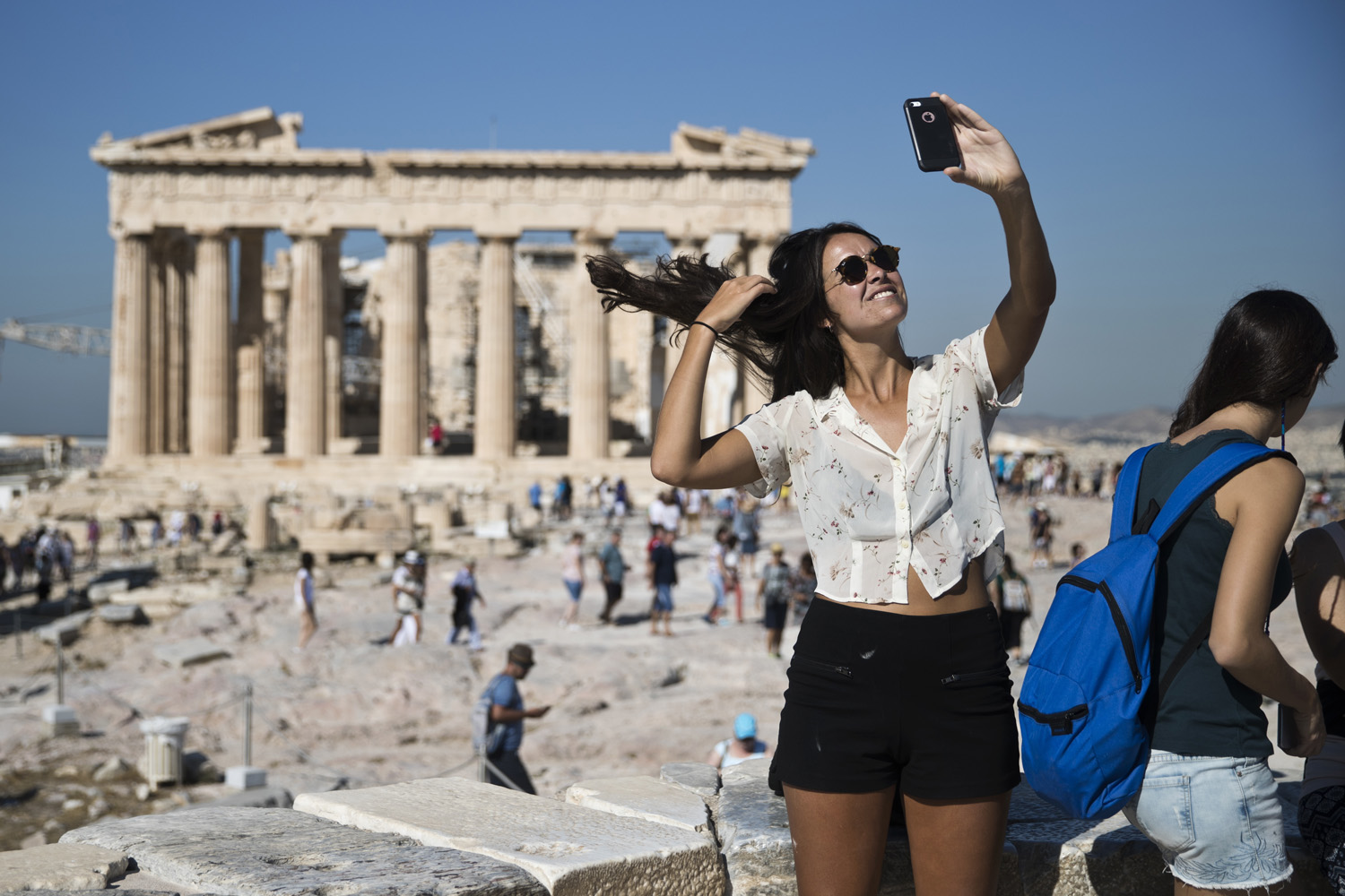 A tourist takes a selfie in front of the the ruins of the fifth century B.C. Parthenon temple at the Acropolis hill, on Friday, Sept. 1, 2017. (AP Photo/Petros Giannakouris)