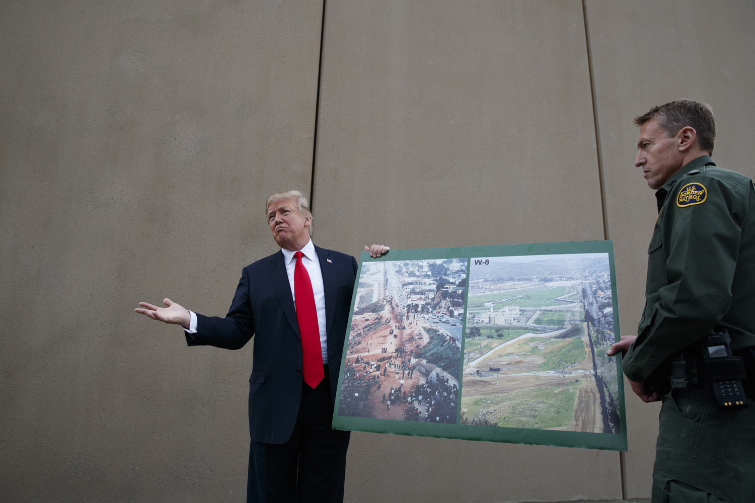 President Donald Trump talks with reporters as he gets a briefing on border wall prototypes, Tuesday, March 13, 2018, in San Diego. (AP Photo/Evan Vucci)