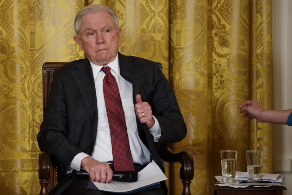 Attorney General Jeff Sessions adjust his jacket before the arrival of President Donald Trump to speak during the White House Opioid Summit in the East Room of the White House, Thursday, March 1, 2018, in Washington. (AP Photo/Evan Vucci)