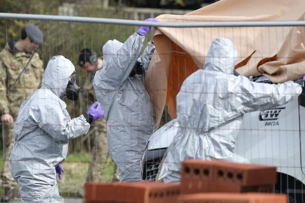 Soldiers wearing protective clothing cover  a tow truck in Hyde Road, Gillingham, Dorset, England as the investigation into the suspected nerve agent attack on Russian double agent Sergei Skripal continues Wednesday March 14, 2018.  The army cordoned off a road in Dorset on Wednesday as the investigated the attack on Sergei Skripal and his daughter Yulia. Authorities have cordoned off several sites in and near Salisbury, 90 miles (145 kilometers) southwest of London as part of their probe.  (Andrew Matthews/PA via AP)