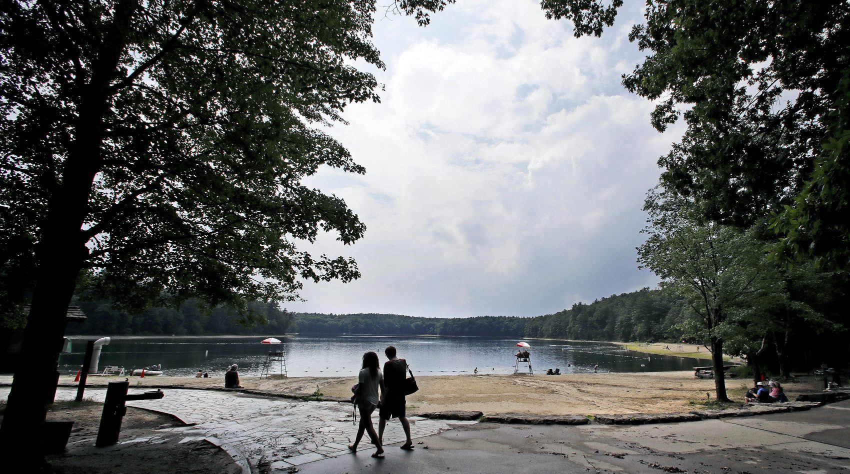A couple walks along the shore of Walden Pond in Concord, Mass. in 2017. (Charles Krupa/AP)