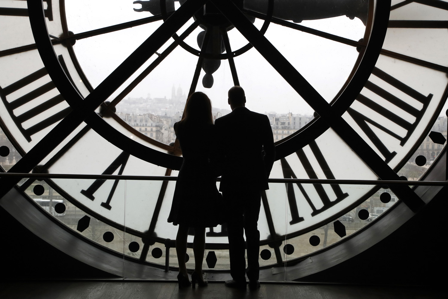 Britain's Prince William, Duke of Cambridge, and his wife Britain's Kate, Duchess of Cambridge, are silhouetted as they look the Seine river through a giant clock at the Musee d'Orsay museum -the former Gare d'Orsay train station- during their visit to the museum, Saturday, March 18, 2017, on the second day of their two-day visit to the French capital. (Francois Guillot/Pool Photo via AP)