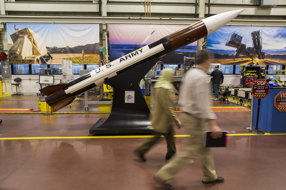 Two Raytheon employees walk past a mock-up of a Patriot missile at the company's Andover facility. Raytheon is the largest producer of guided missiles in the world. (Jesse Costa/WBUR)