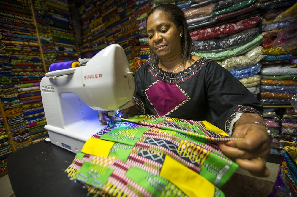 Ebby Ihionu sews a pleated dance skirt at Elegance African Fashions in Dorchester. She's run the store for 11 years and has seen an increase in business since the movie Black Panther came out. (Jesse Costa/WBUR)