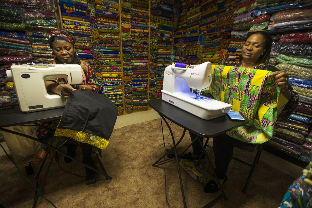 Ebby Ihionu, right, and her sister Ifeyinwa Okolie work on custom clothes made with African fabrics at Elegance African Fashions in Dorchester. (Jesse Costa/WBUR)