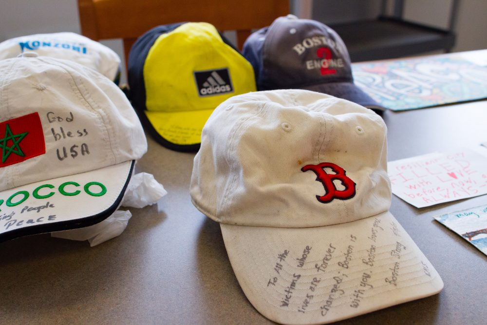 Hats and signs that were left at the pop-up memorial for the Boston Marathon bombing are arranged on tables at the Boston City Archives. (Elizabeth Gillis/WBUR)