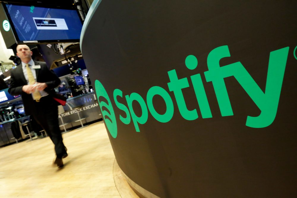 A trading post sports the Spotify logo on the floor of the New York Stock Exchange, Tuesday, April 3, 2018. Spotify, the No. 1 music streaming service which has drawn comparisons to Netflix, is about to find out how it plays on the stock market in an unusual IPO. (Richard Drew/AP)