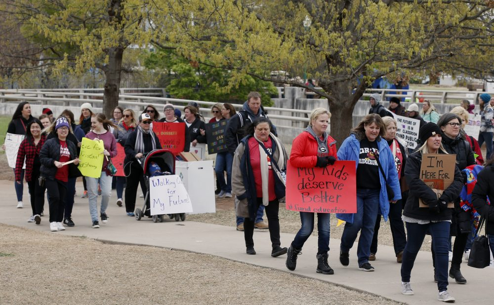 Supporters carry signs as they picket around the state Capitol during a teacher's rally in Oklahoma City, Monday, April 2, 2018. Teachers were holding separate protests in Oklahoma and Kentucky on Monday to voice dissatisfaction with issues like pay and pensions. (AP Photo/Sue Ogrocki)