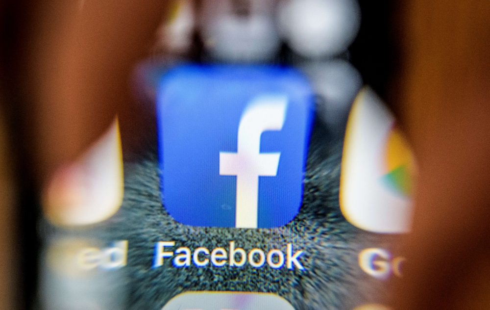 The icon for the social networking app Facebook on a smartphone screen, photographed through a magnifying glass. (Mladen Antonov/AFP/Getty Images)