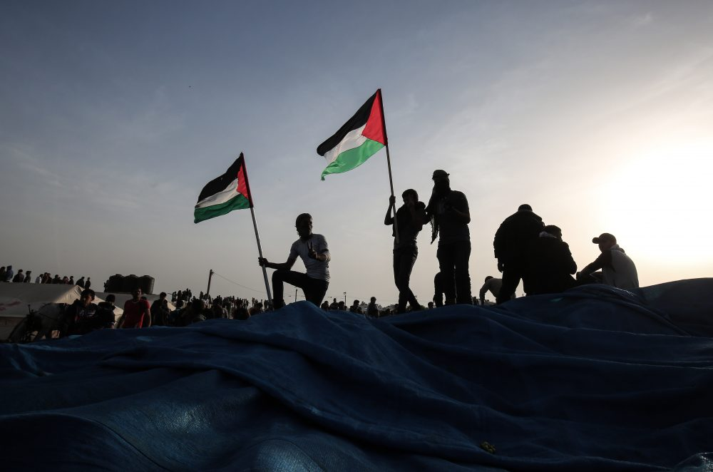 A Palestinian protester waves his national flag at the site of a tent protest, near the border with Israel, east of Khan Yunis, in the southern Gaza Strip on April 4, 2018. (Said Khatib/AFP/Getty Images)