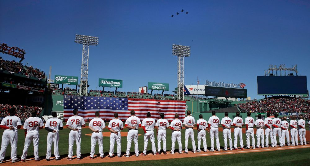Boston Red Sox players line up along the first base line as four F-16's, from the Air National Guard's 134th Fighter Squadron in Burlington, Vermont, fly over during ceremonies prior to a home opener. (Charles Krupa/AP)