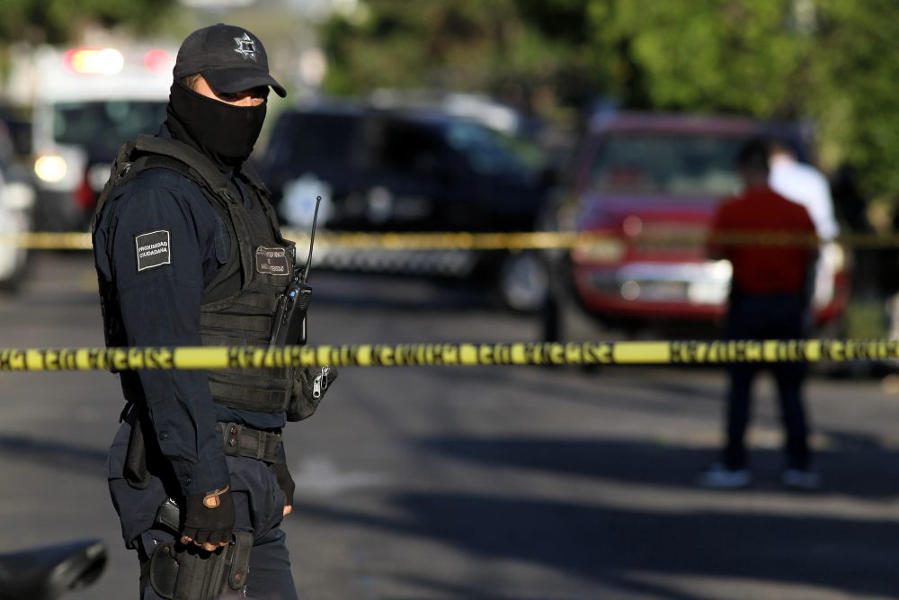 A police officer stands guard as state prosecutors inspect a pickup truck found abandoned with the bodies of six men, some of them decapitated, which are thought to have been killed by alleged traffickers of a rival cartel, in the Morelos neighborhood in Guadalajara, Mexico, on March 6, 2018. Mexico has suffered a wave of violence linked to drug trafficking that has intensified in recent years. (Ulises Ruiz/AFP/Getty Images)