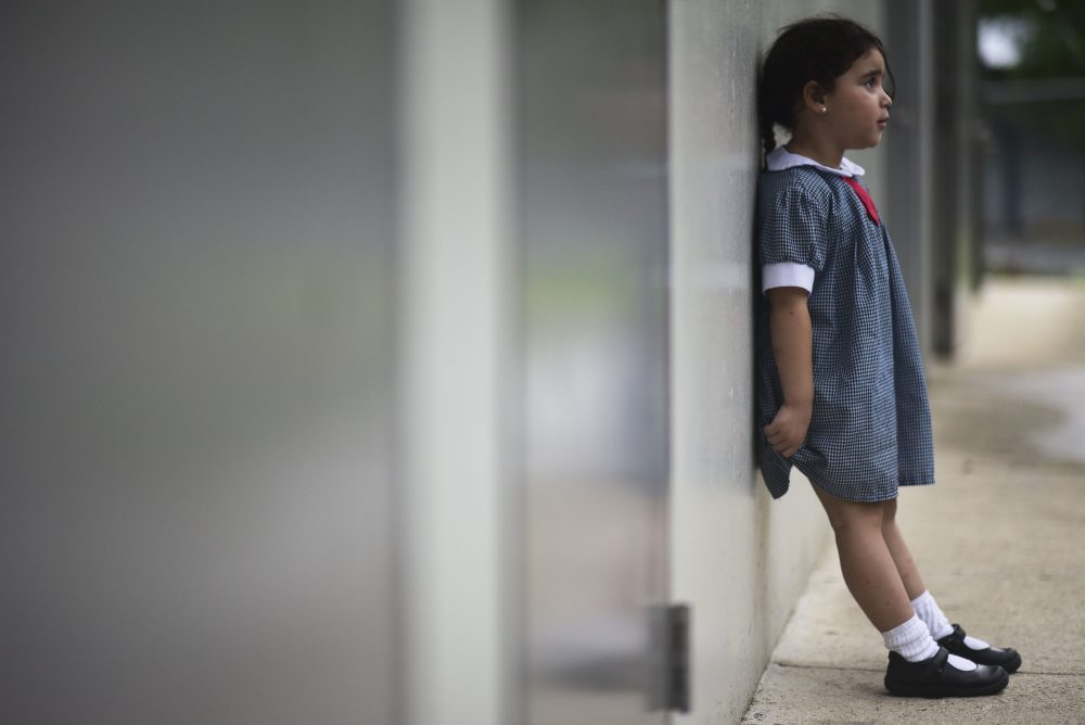 In this Friday, Oct. 13, 2017 photo, a girl waits for her mother in the hallway of Ramon Marin Sola Elementary School, which opened its doors as a daytime community center after the passing of Hurricane Maria in Guaynabo, Puerto Rico. (Carlos Giusti/AP)