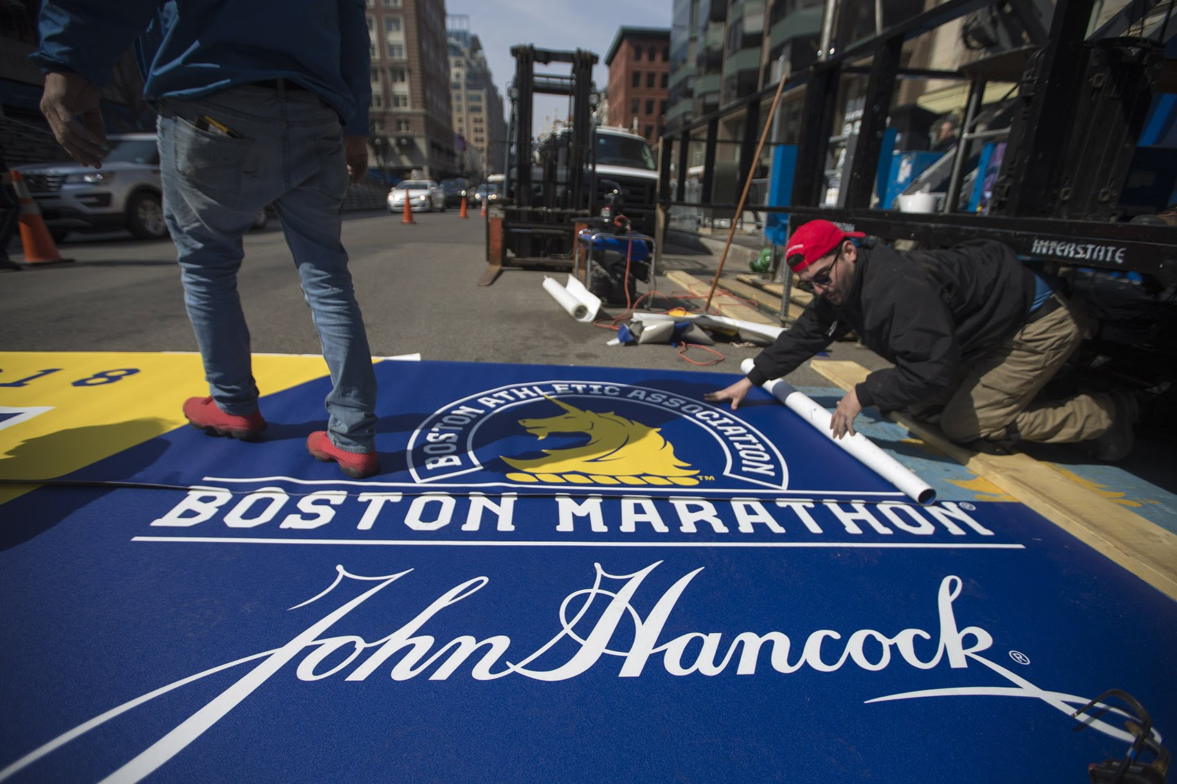 Workers lay down the new finish line for the 2108 Boston Marathon. (Jesse Costa/WBUR)