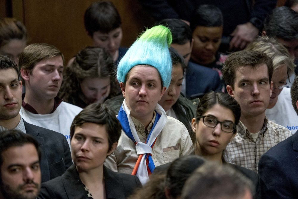Ian Madrigal seen wearing a blue and green pointy wig, aiming to look like a Russian troll, as Facebook CEO Mark Zuckerberg testifies before a joint hearing of the Commerce and Judiciary Committees on Capitol Hill in 2018. (Andrew Harnik/AP)