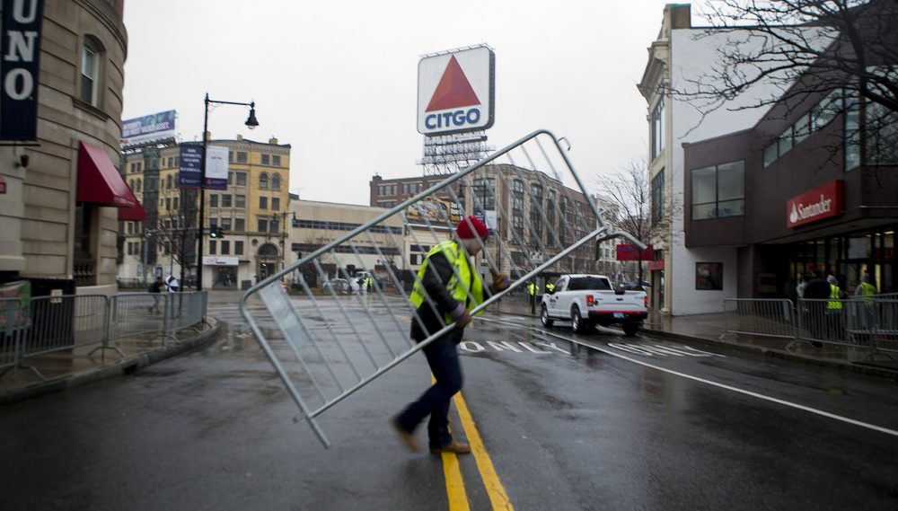 Workers set up barriers along Brookline Avenue in Kenmore Square. (Jesse Costa/WBUR)
