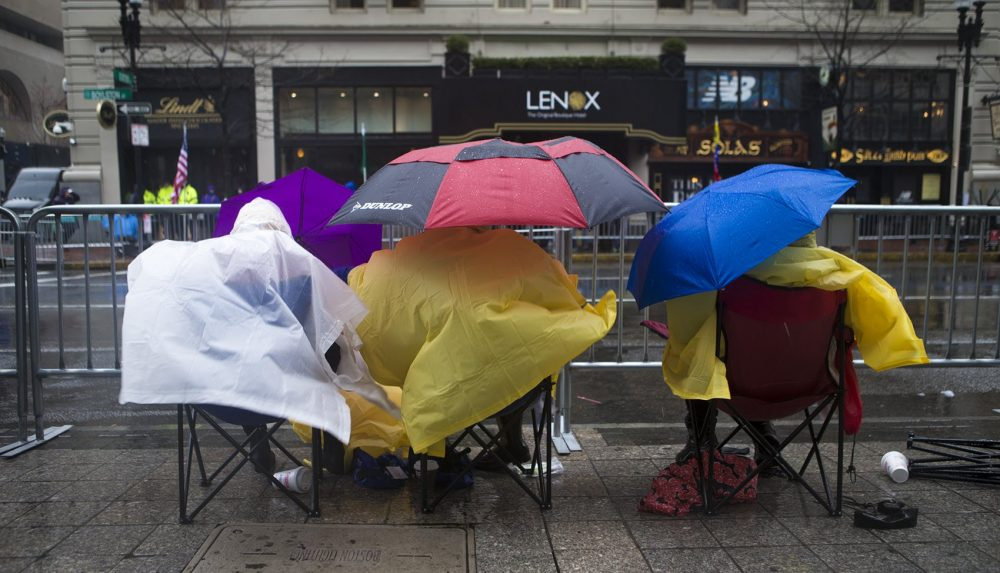 Spectators camp out in the wind and rain along Boylston Street. (Jesse Costa/WBUR))