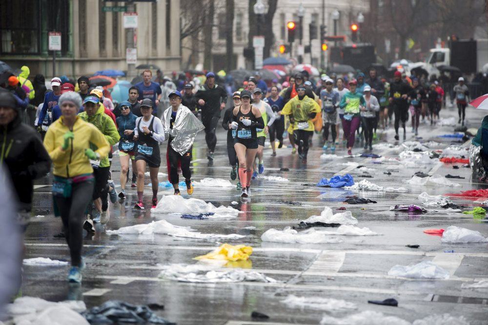 Marathoners run up a plastic poncho-littered Hereford Street not far from the finish line. (Jesse Costa/WBUR)