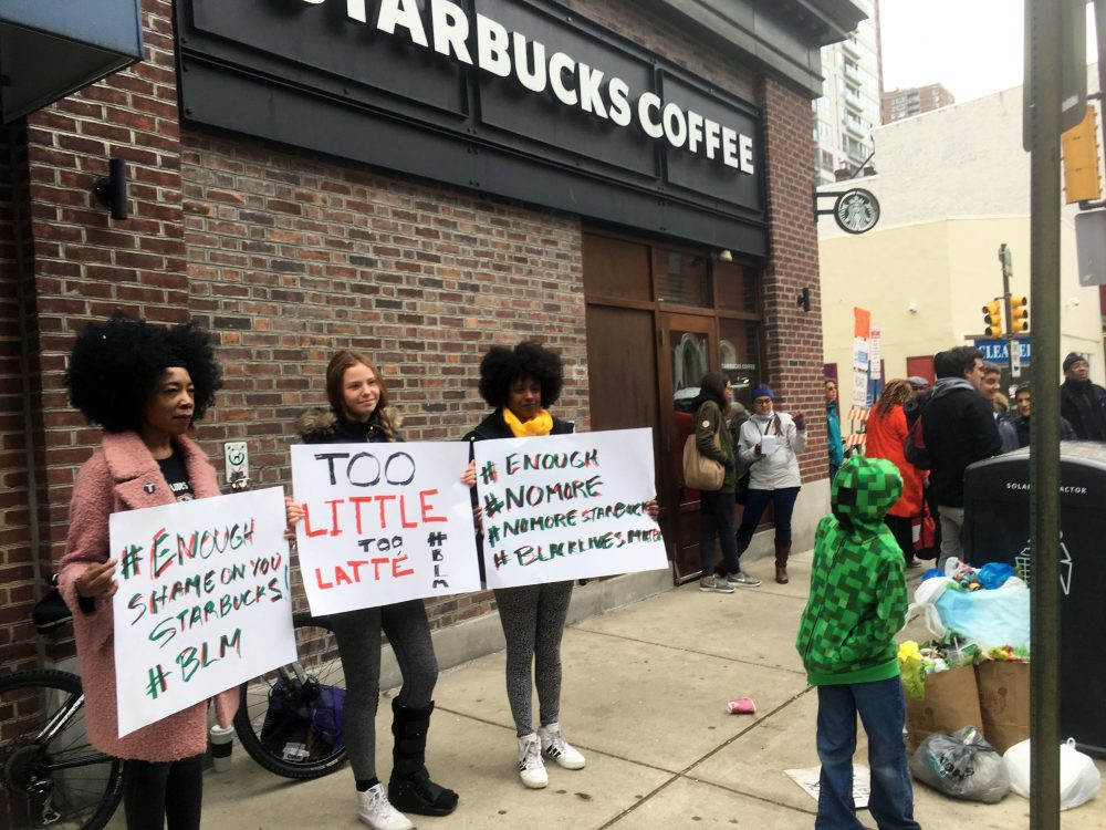 "Protesters gather outside a Starbucks in Philadelphia, Sunday, April 15, 2018, where two black men were arrested Thursday after Starbucks employees called police to say the men were trespassing. The arrest prompted accusations of racism on social media. Starbucks CEO Kevin Johnson posted a lengthy statement Saturday night, calling the situation ""disheartening"" and that it led to a ""reprehensible"" outcome. (AP Photo/Ron Todt)"