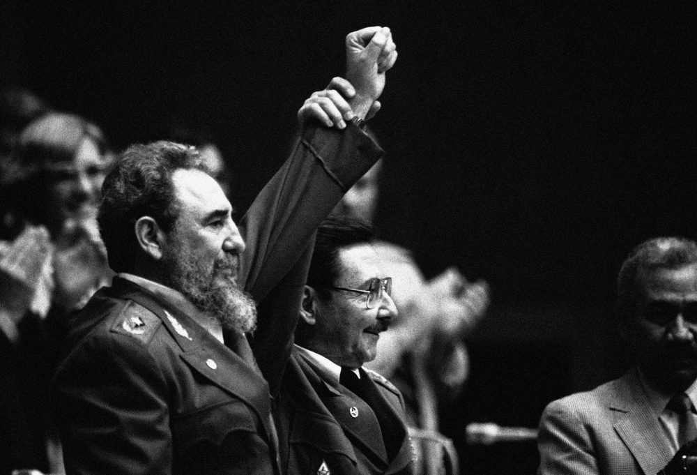 In this Feb. 8, 1986 file photo, Cuban President Fidel Castro, left, joins hands with his younger brother Raul Castro, chief of the Cuban Armed Forces and first vice president, after the two were reelected in the Third Cuban Communist Party Congress session in Havana, Cuba. (AP Photo/Charles Tasnadi, File)