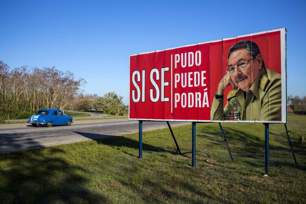 """A car drives by a billboard that reads in Spanish """"It was, is and will be done"""" with a picture of Cuba's President Raul Castro on the outskirts of Havana, Cuba, Wednesday, April 18, 2018. Cuba's legislature opened the two-day session that is to elect a successor to President Castro. (Desmond Boylan/AP)"""