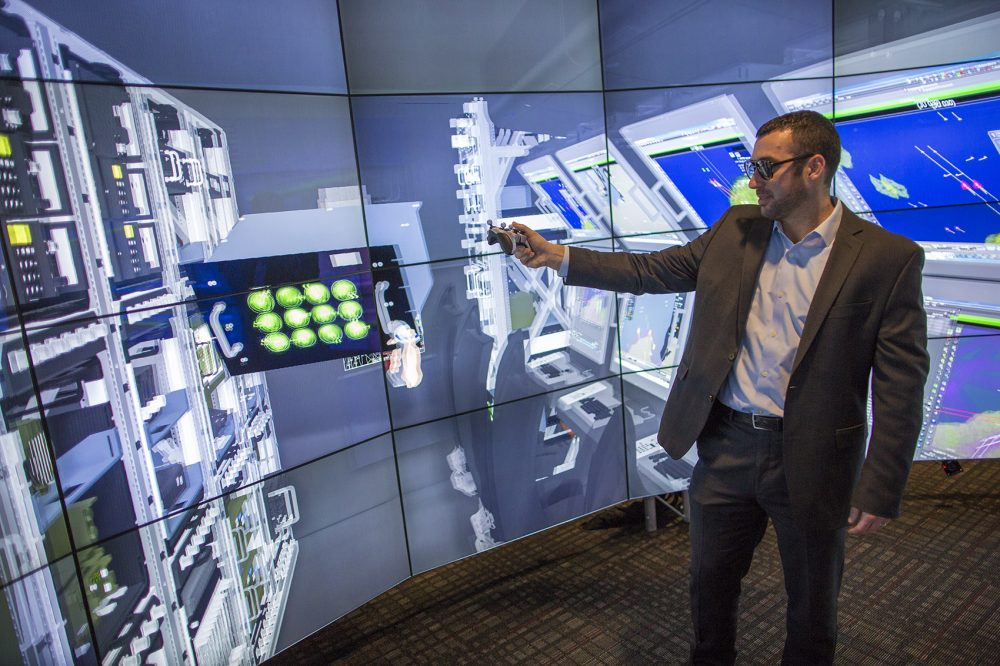 Dan Gale, manager of the Immersive Design Center, demonstrates the interactive features of Raytheon's Customer Automatic Virtual Environment (CAVE). (Jesse Costa/WBUR)