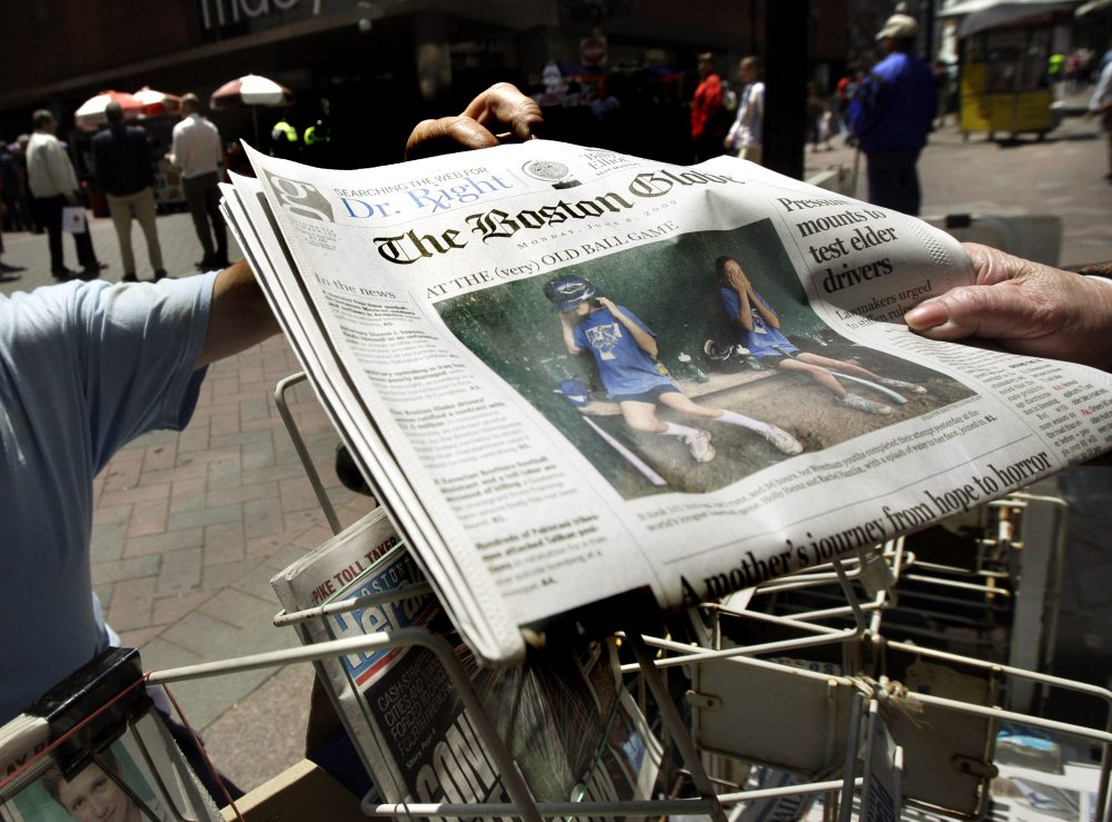 A customer buys a Boston Globe newspaper from a street newsstand in Boston's Downtown Crossing in 2009. (Elise Amendola/AP)